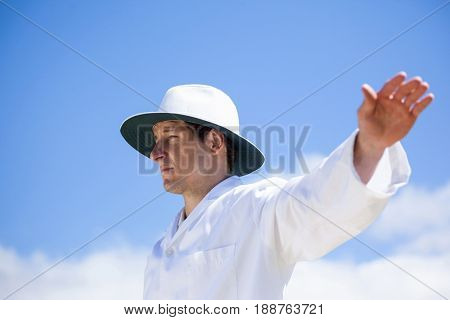 Low angle view of cricket umpire signalling a boundary at match