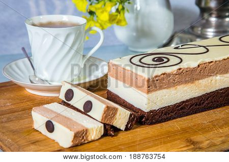 Holiday cake Three-colate. Three-layer chocolate cake, decorated with chocolate patterns. Background -  vase with flowers and porcelain cup with hot tea. Professional bakery