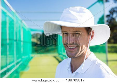 Portrait of smiling cricketer standing at field on sunny day