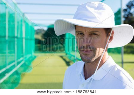 Portrait of cricketer standing at field on sunny day