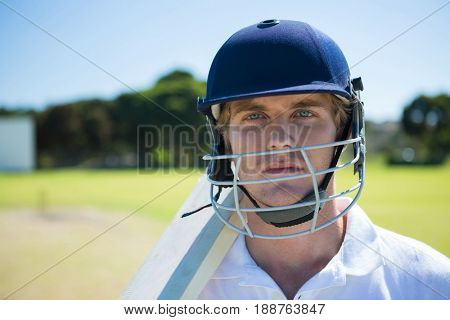 Portrait of cricket player holding bat while wearing helmet at field on sunny day