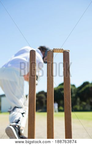 Close up of stump by batsman standing on field against clear sky