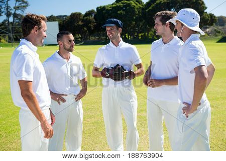 Cricket players standing at field against clear sky