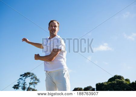 Man bowling while standing on cricket field against sky