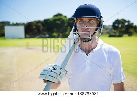 Thoughtful cricket player holding bat while wearing helmet at field on sunny day