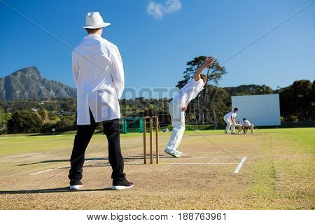Sports team playing cricket on pitch against sky on sunny day