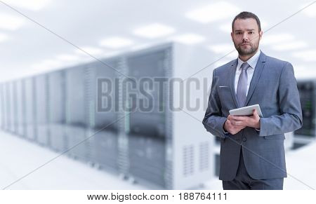 Portrait of young businessman in server room using tablet