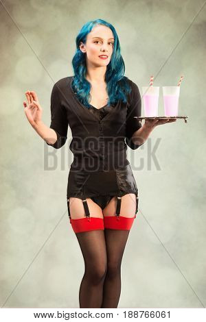 Cheeky pin up girl holding a silver tray of glasses filled  with strawberry milkshakes