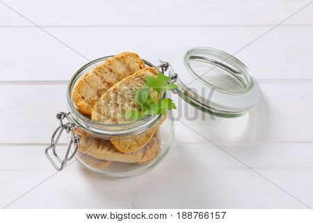 jar of crispy rusks on white wooden background