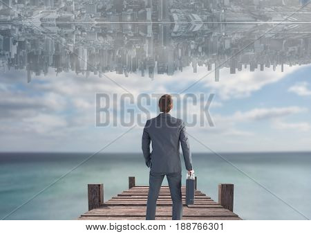 Digital composite of up side down city in the sky over the sea with dock. Men looking up.