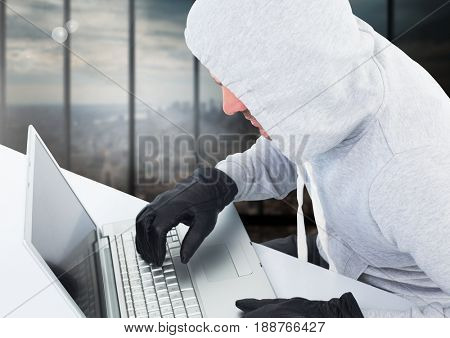 Digital composite of Criminal in hood with laptop in front of window