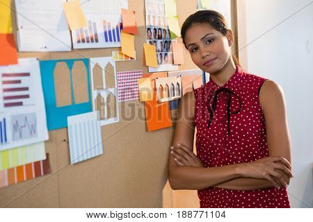Portrait of female executive leaning on bulletin board with arms crossed in office