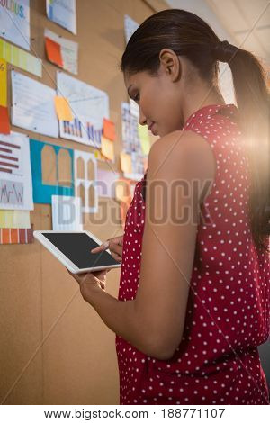 Female executive using digital tablet near bulletin board in office