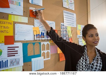Female executive pointing at sticky note on bulletin board at office