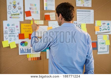 Rear view of male executive pointing at bulletin board in office