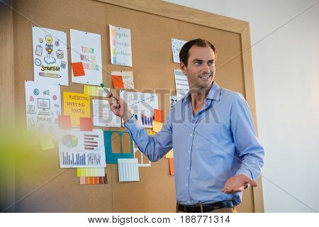 Male executive explaining the graph on bulletin board at office