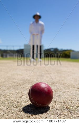 Cricket ball on pitch with umpire standing in background against clear blue sky