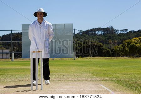 Full length of umpire standing behind stumps during cricket match on sunny day