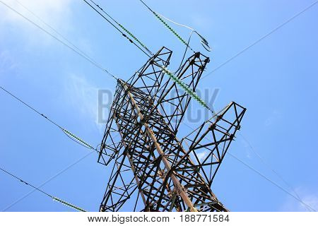 Transmission power tower electricity pylon over blue sky. Steel lattice tower used to support an overhead power line