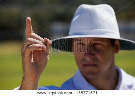 Umpire gesturing out sign during match on sunny day