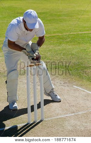 Full length of wicketkeeper catching ball behind stumps on field during sunny day