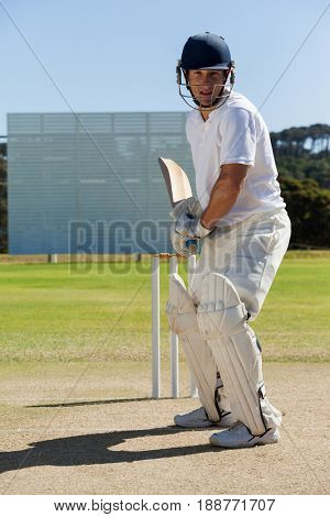 Concentrated player playing cricket on field against clear sky during sunny day