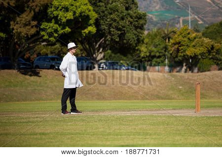 Full length of umpire standing on cricket field during sunny day