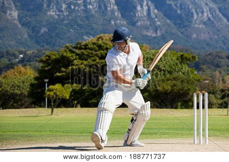 Full length of cricket player playing on field during sunny day