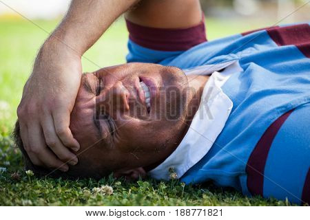 Injured rugby player with eyes closed lying on playing field