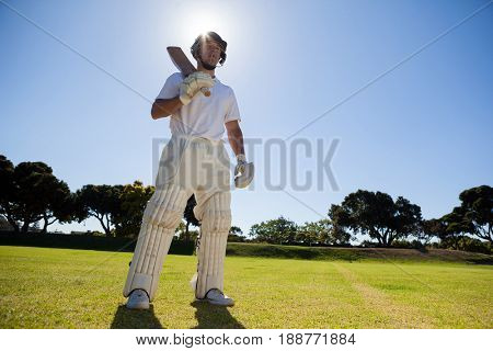 Low angle view of confident player with cricket bat standing against blue sky