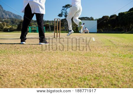 Close up of team playing cricket on pitch against sky on sunny day