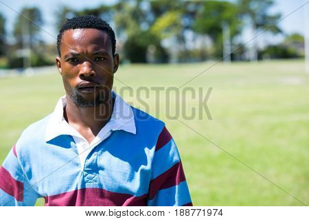 Portrait of serious rugby player standing at field on sunny day