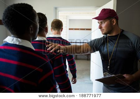Coach motivating rugby team while standing at locker room