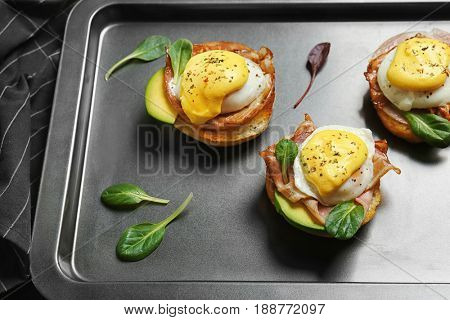 Eggs Benedict with basil leaves on baking pan