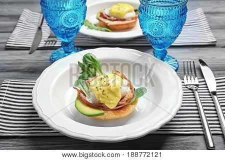Tasty egg Benedict with cutlery on table