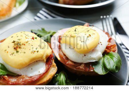 Tasty eggs Benedict on plate