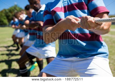 Midsection of rugby players playing tug of war on field