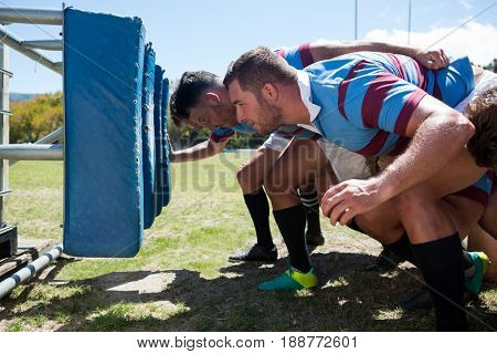 Side view of rugby players crouching at field on sunny day