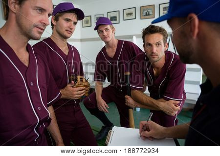 Close up of confident baseball team planning with coach while standing at locker room