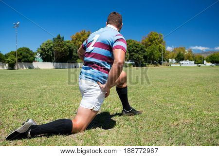 Rear view of rugby player exercising while kneeling on grassy field against sky