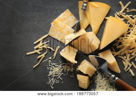 Composition with pieces of different cheese on grey background
