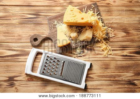 Grater and cutting board with cheese on wooden background