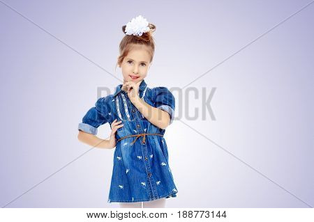 The little blonde girl with a large white bow on the head and short denim dress.She holds a finger to his cheek.Purple gradient background.
