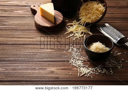 Bowls with cheese, cutting board and grater on wooden background