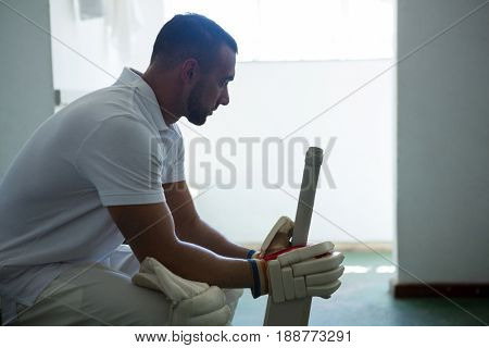Side view of cricket player sitting on bench at locker room