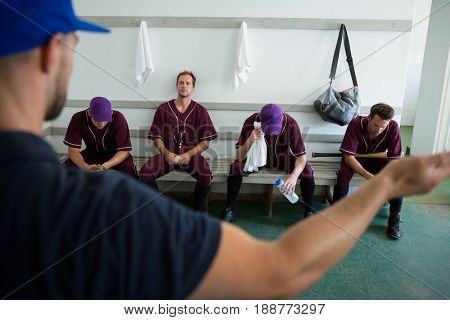 Rear view of coach discussing with baseball team at locker room