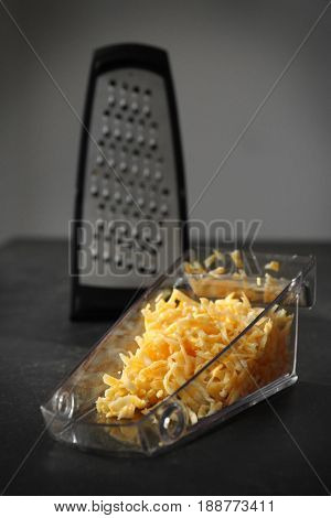 Plastic container with cheese and grater on table