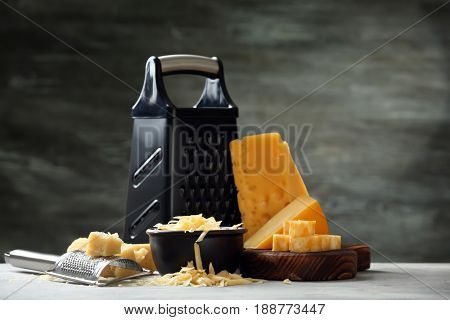 Cutting board with cheese, bowl and graters on grey background