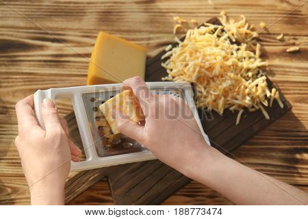 Woman grating cheese on wooden table