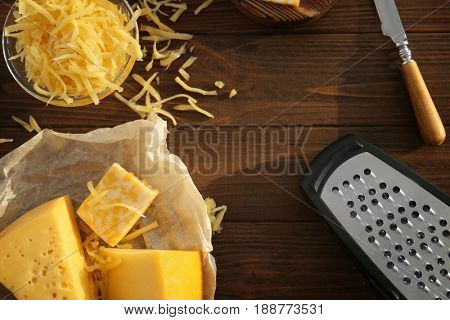 Parchment with different types of cheese and grater on wooden table